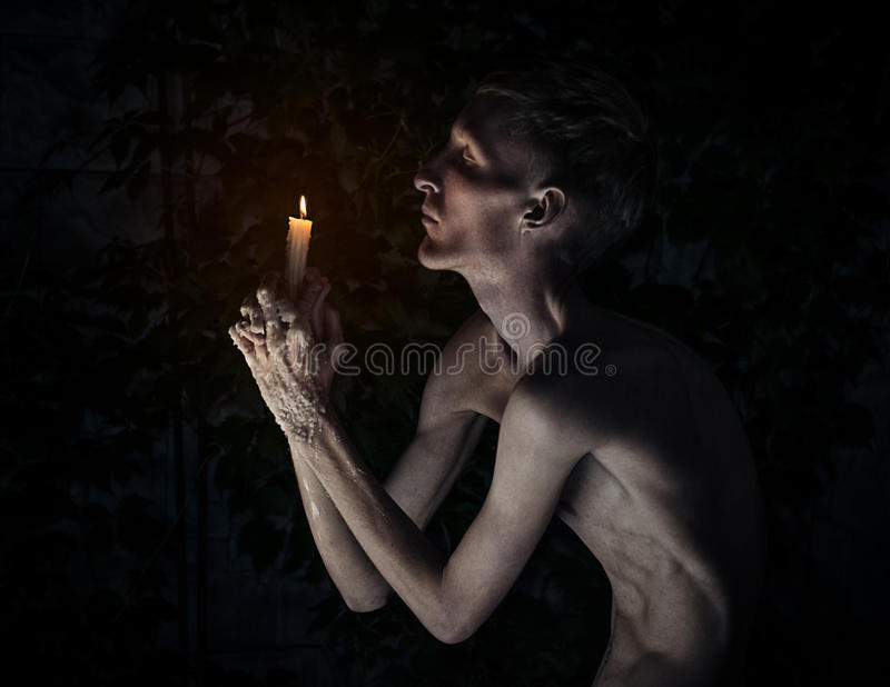 Gothic and Halloween theme: a man with a candle on his knees with his eyes closed and praying, hot wax on his hands. Studio royalty free stock image