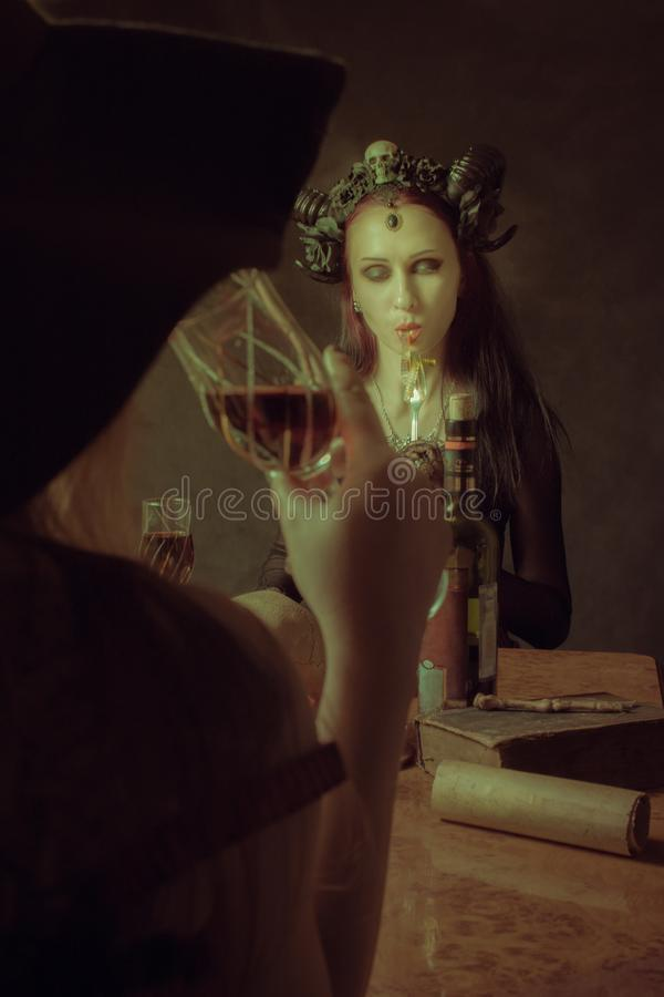 Dinner with Satan. Gothic horned girl eating worms over dark background stock photos