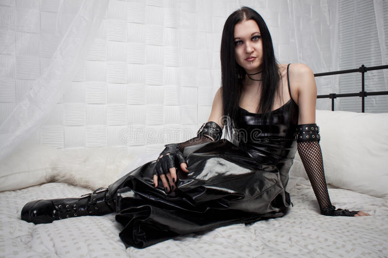 Gothic lady. Beautiful gothic lady in latex sits on the bed stock images