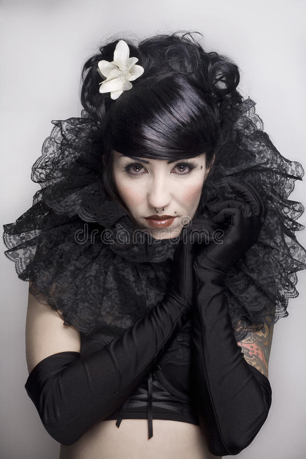 Gothic lolita. Beautiful headshot of a black hair girl dressed in a gothic lolita style with gloves and a flower in her hair royalty free stock image
