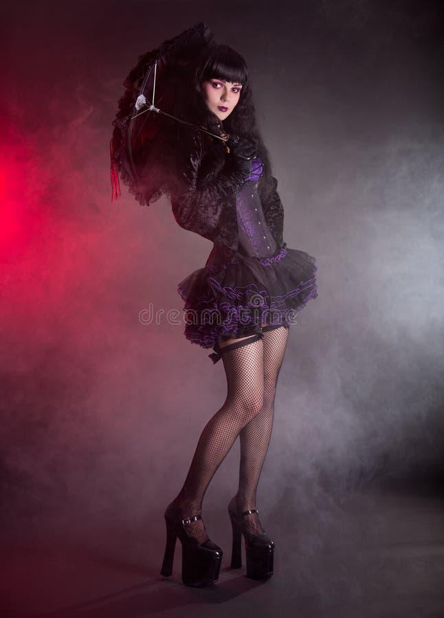 Gothic Lolita girl with lace umbrella. Studio shot on black background stock photo