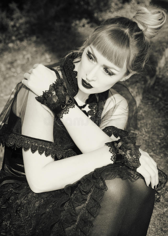 Gothic lolita portrait. Portrait of beautiful and dark Gothic Lolita doll with Cuffs on her hands in black and white stock photos