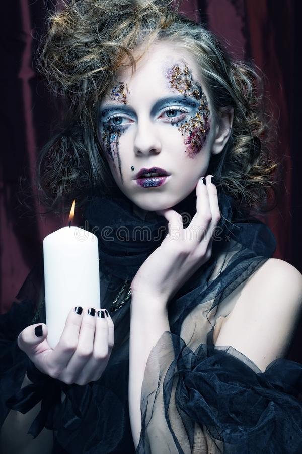 Gothic portrait of woman with candle. Halloween theme stock photo