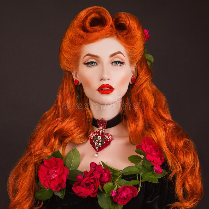 Gothic queen with red lips with stylish hairstyle in studio. Beauty redhead model with hairdo on black background. royalty free stock image
