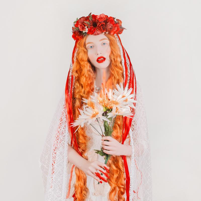Gothic redhead woman vampire in flower wreath with pale skin and red lips. Vampire with burn fire bouquet. Gothic witch in wreath royalty free stock image