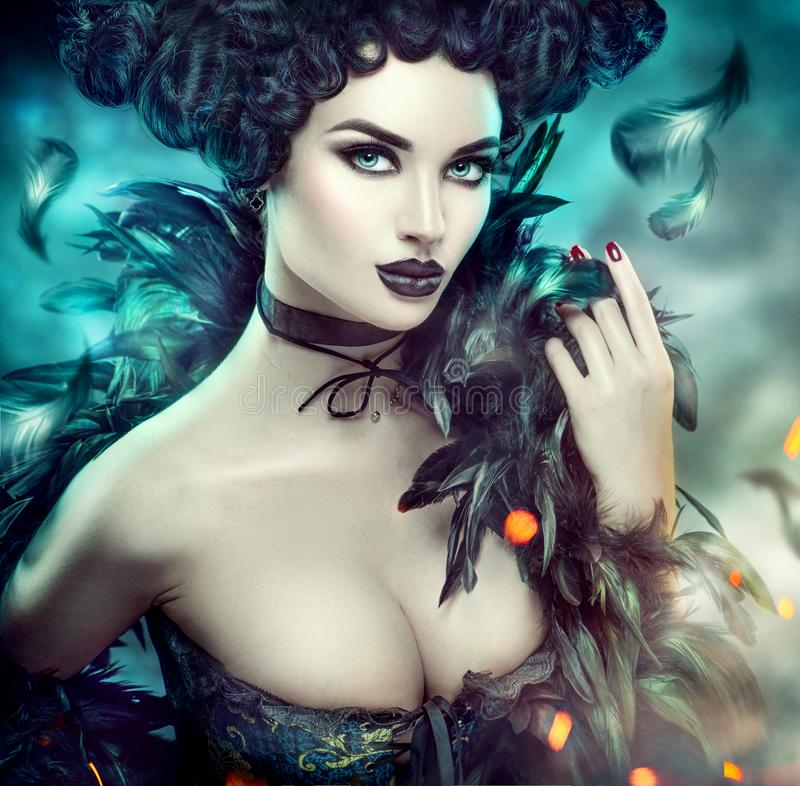 Gothic sexy young woman. Halloween. Beautiful model girl with fantasy makeup in goth costume with black feathers royalty free stock photography