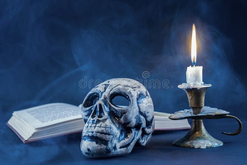 Gothic skull and candle in candlestick burning and book in background, dark and smoked scene royalty free stock photo