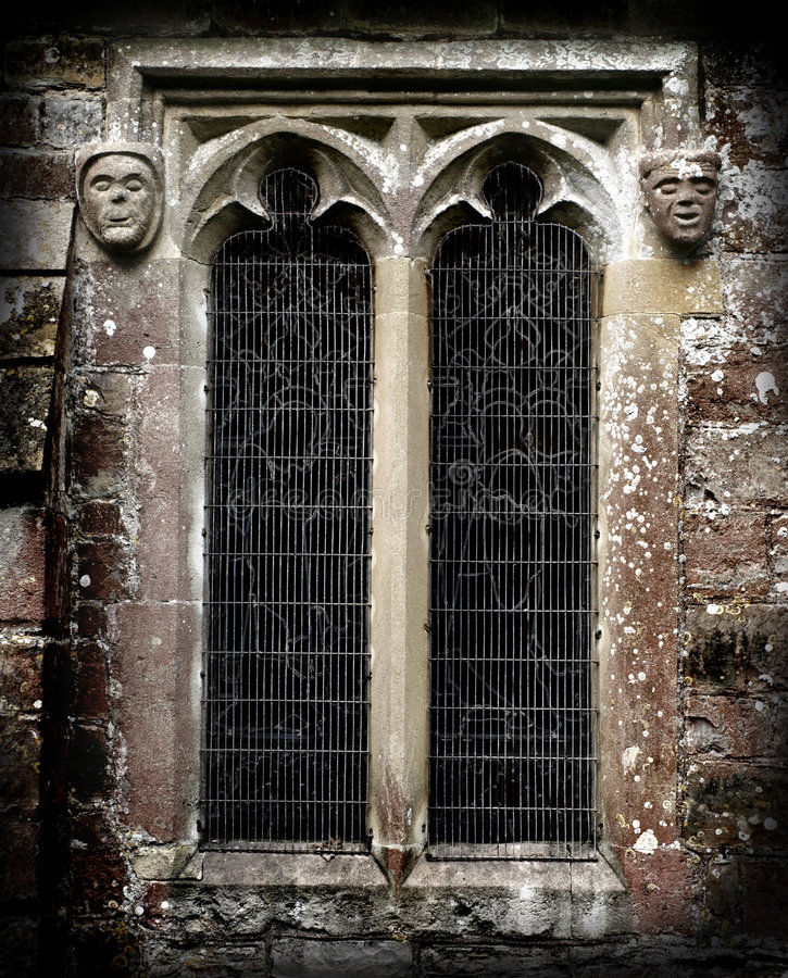 Gothic Stone Faces next to a church window. Gothic Stone Faces next to a window and a Church wall stock image
