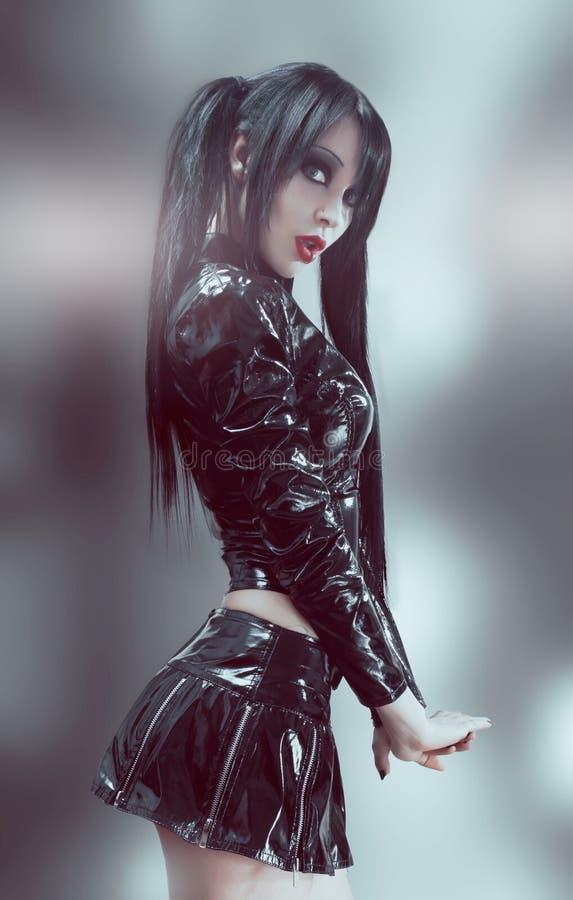 Gothic studio portrait of brunette woman. In black vinyl costume royalty free stock photos