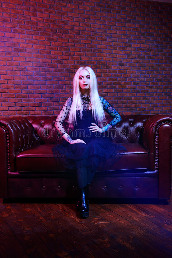 Gothic style lady. Portrait of an extravagant attractive woman with bright make-up and long blonde hair. Beauty, fashion concept. Cosmetics, make-up. Gothic royalty free stock photography