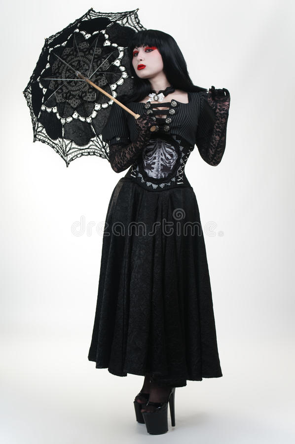 Gothic vampire girl in black dress with umbrella. Gothic vampire girl in black dress with black umbrella stock image