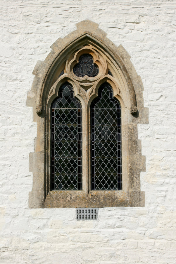 Gothic Window. Gothic leaded glass window on the outside of a church set within a white washed stone wall stock photos