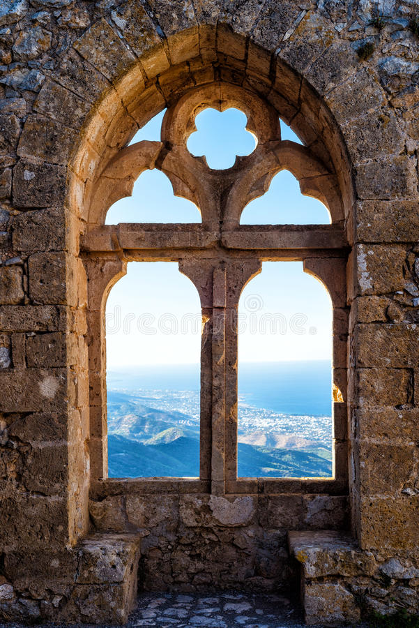 Gothic window with a mountain view. Gothic window of a castle with a mountain view stock photography