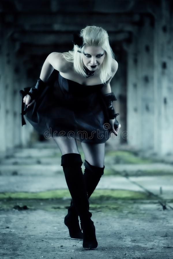 Gothic witch woman. With spooky make-up in black dress stock photography