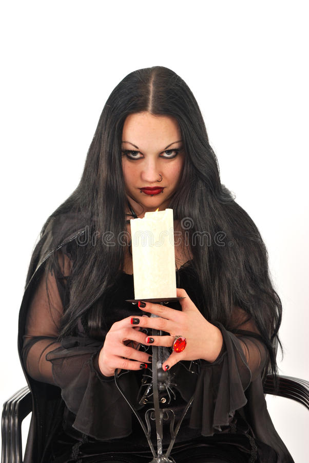 Gothic woman. Gothic girl with large candle royalty free stock images