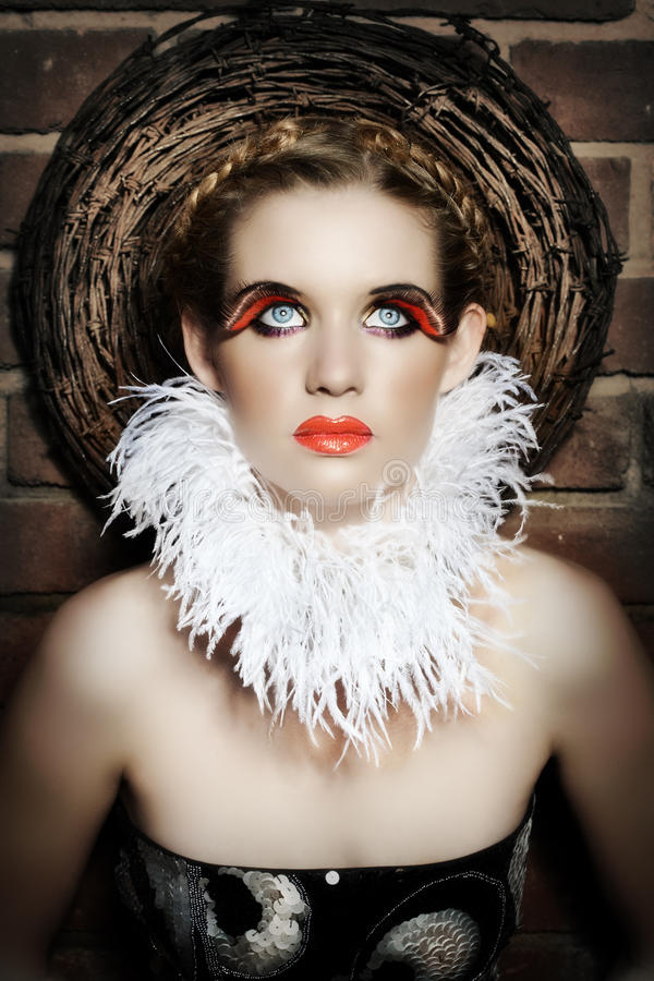 Gothic woman. Gothic beautiful woman with feather necklace and false lashes wearing red lips stock photos