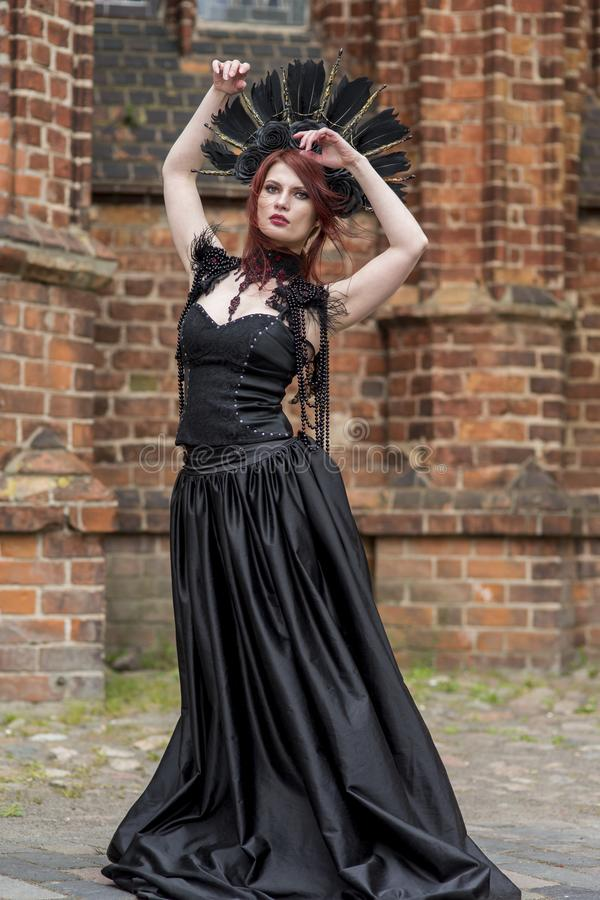 Gothic Woman in Black Dress and Feather Crown.Against Brick Wall Outdoors. Posing with Lifted Hands. Vertical Image royalty free stock photography
