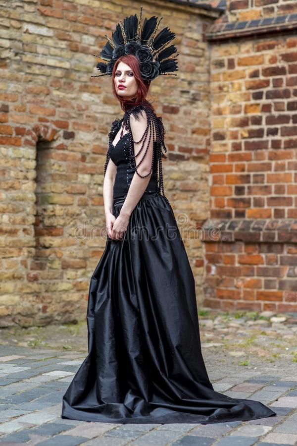 Gothic Woman in Black Dress and Feather Crown. Against Brick Wall Outdoors. Vertical Image royalty free stock image