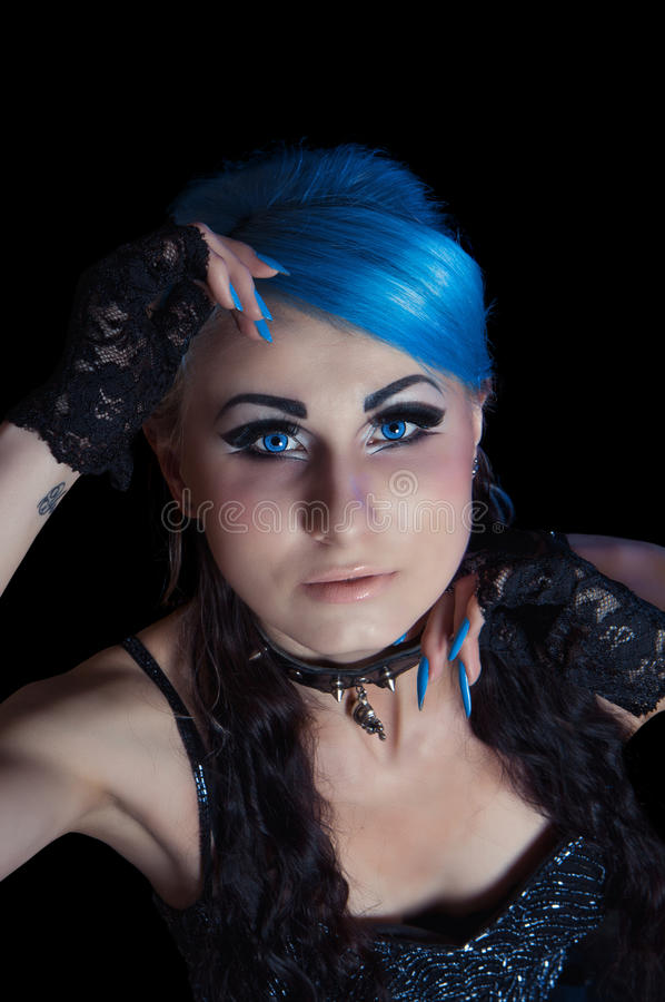 Gothic woman with blue hairs and manicure. Portrait of beautiful young gothic woman with blue hairs and bright makeup closeup, isolated on black royalty free stock photography