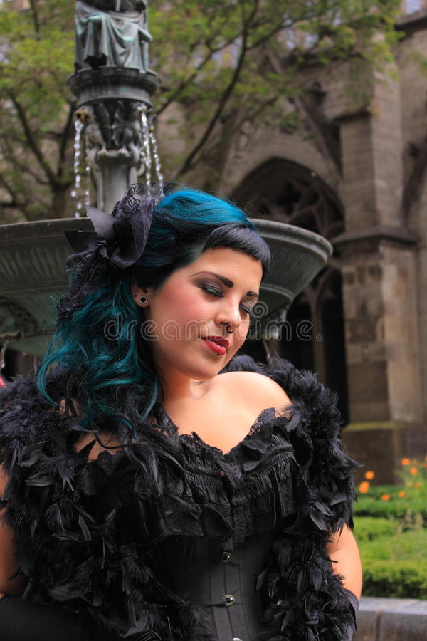 Gothic woman with boa. Beautiful gothic girl with black boa in a garden of a church during the gothic festival summer darkness in the dutch city utrecht, the stock photography