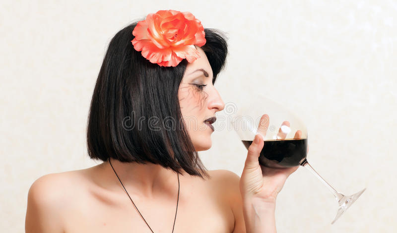 Gothic woman with a glass of wine. Gothic beautiful woman with a flower in her hair holding a glass of wine royalty free stock photo