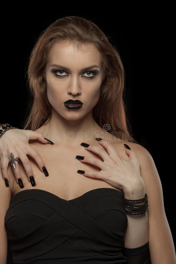 Gothic woman with hands of vampire on her body. Portrait of a gothic woman with hands of vampire on her body on black background.Halloween royalty free stock image