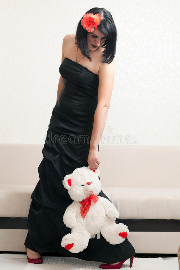 Gothic woman holding a teddy bear. Beautiful gothic woman in a black dress holding a teddy bear stock photography