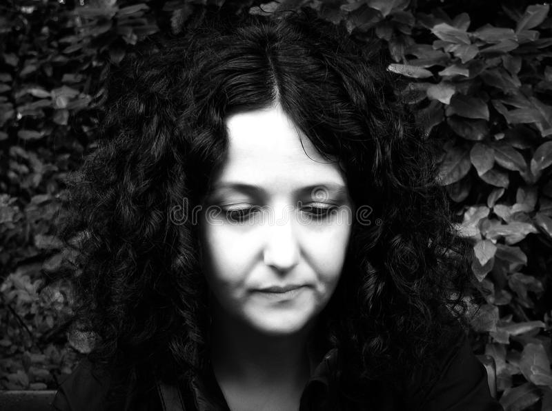 Gothic woman. Low key high contrast black and white portrait of dark goth woman with leaves in the background royalty free stock photos