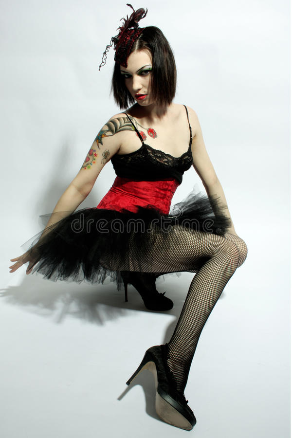 Gothic young woman. Young tattooed woman wearing Gothic style dress, studio background stock photography