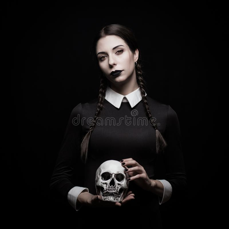 Gothic young woman. Young woman with pale skin with skull, gothic theme, mysteryous atmosphere royalty free stock photo