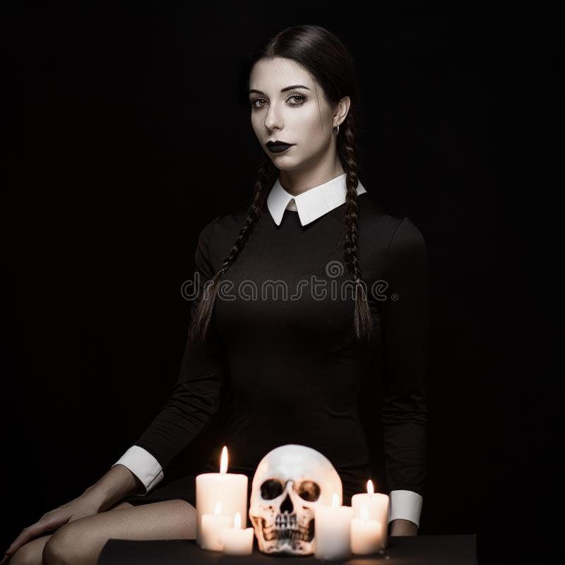 Gothic young woman. Young woman with pale skin with skull, gothic theme, mysteryous atmosphere stock images