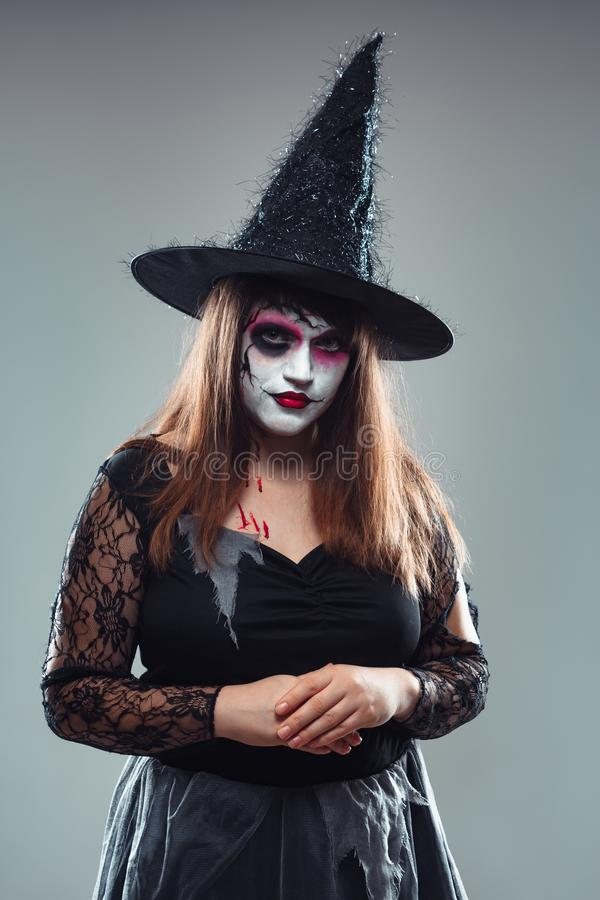 Gothic young woman in witch halloween costume with hat standing. Over gray background, woman in carnival costume of witch or dead bride, halloween portrait of royalty free stock image