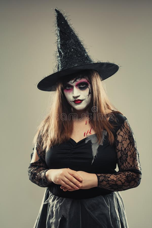 Gothic young woman in witch halloween costume with hat standing over gray background, woman in carnival costume of witch or dead. Bride, halloween portrait of stock images