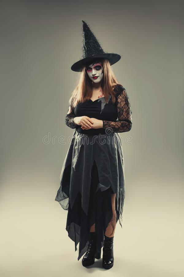 Gothic young woman in witch halloween costume with hat standing over gray background, woman in carnival costume of witch or dead. Bride, halloween portrait of royalty free stock image