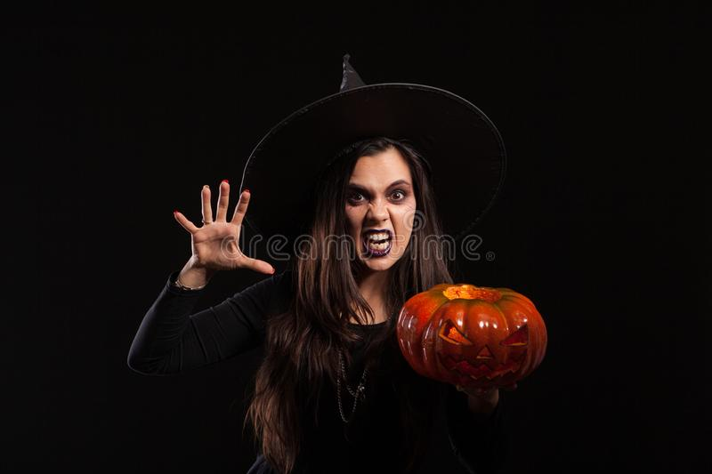 Gothic young woman in witch halloween costume standing over black background. Witch woman holding horror pumpkin stock photo
