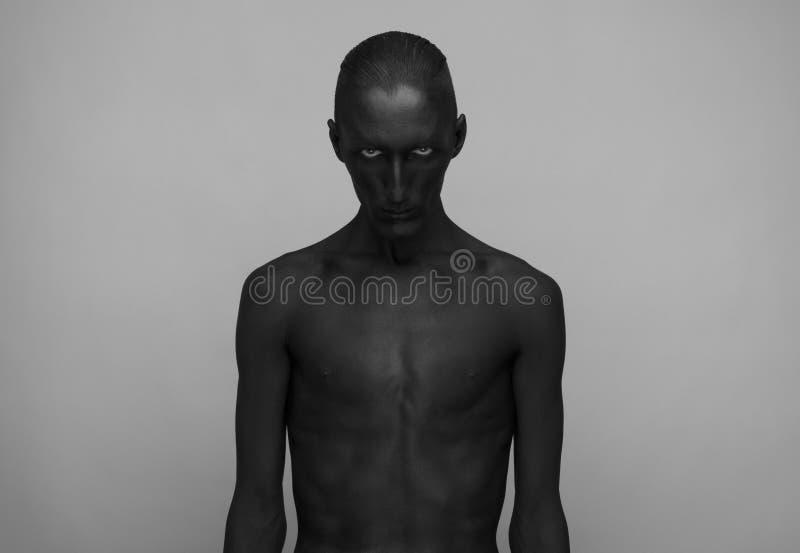 Gotisch en Halloween-thema: een mens met zwarte huid is geïsoleerd op een grijze achtergrond in de studio, het art. van het Zwart stock foto
