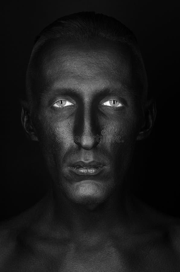 Gotisch en Halloween-thema: een mens met zwarte huid is geïsoleerd op een zwarte achtergrond in de studio, het art. van het Zwart royalty-vrije stock afbeelding