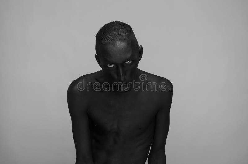 Gotisch en Halloween-thema: een mens met zwarte huid is op een grijze achtergrond in de studio, het art. van het Zwarte Doodlicha royalty-vrije stock afbeeldingen
