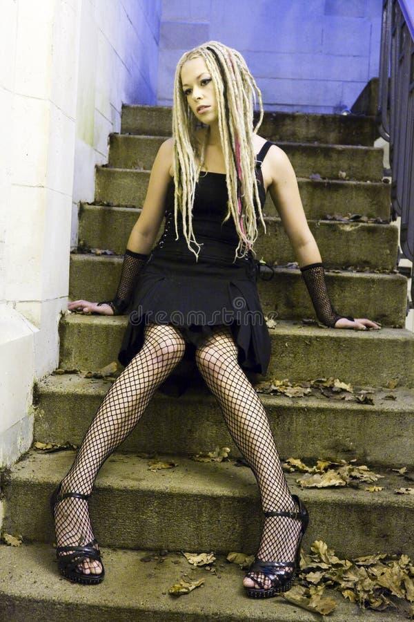Gotische Frau, die auf Jobstepps sitzt lizenzfreie stockfotografie