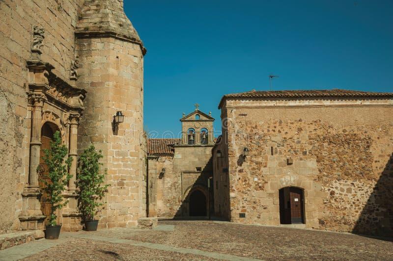 Gotische Kirchenfassade mit Holztür und Altbau in Caceres stockbilder