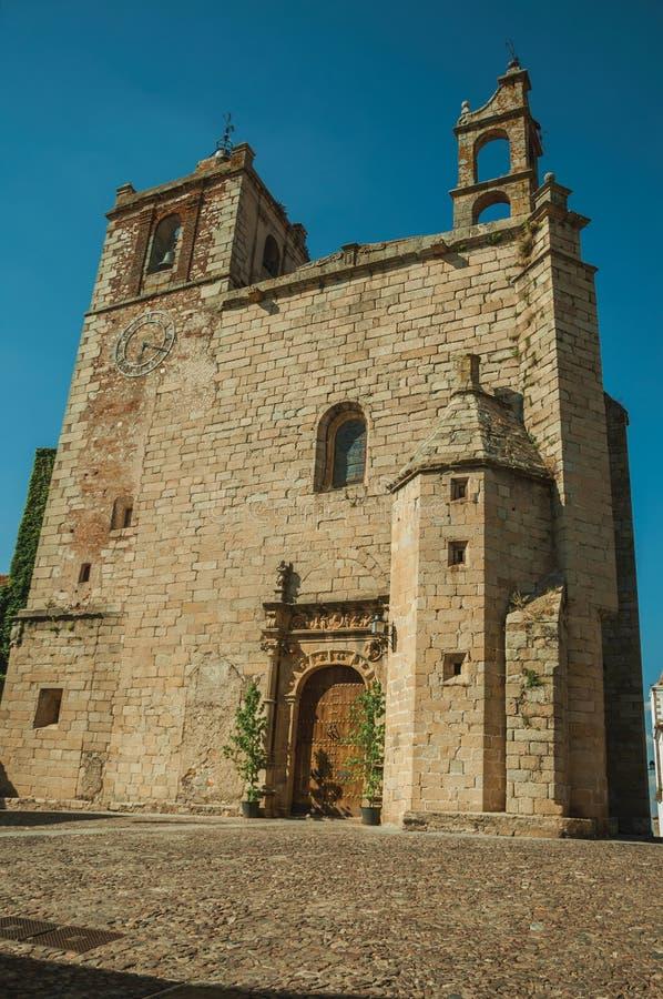 Gotische Kirchenfassade mit Kirchtürmen und Holztür in Caceres lizenzfreies stockbild