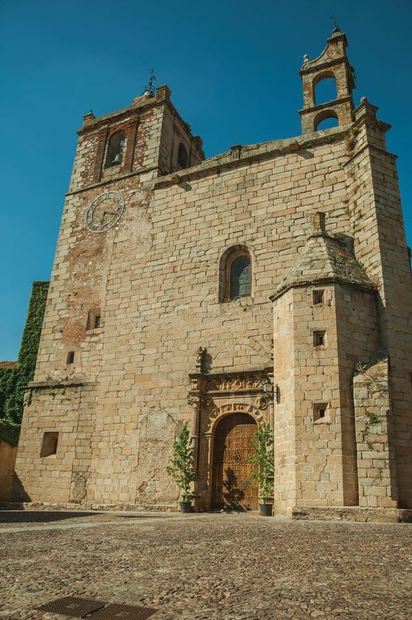 Gotische Kirchenfassade mit Kirchtürmen und Holztür in Caceres lizenzfreie stockfotos