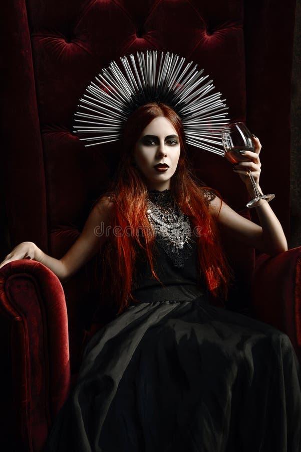 Gotische Mode: junge Frau, die im Stuhl sitzt und Glas Wein hält lizenzfreie stockfotos