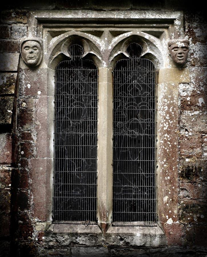 Gotische Steingesichter nahe bei einem Kirchefenster stockbild