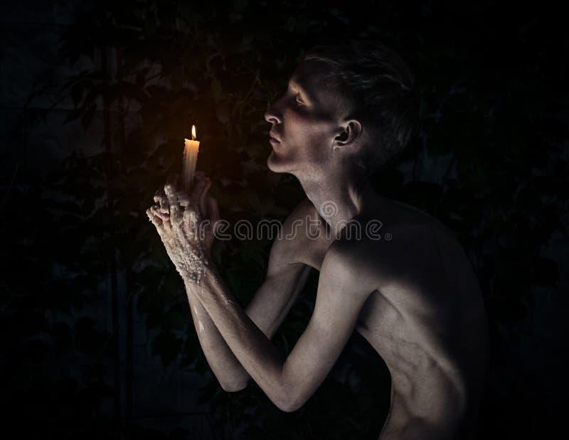 Gotisk och allhelgonaaftontema: en man med en stearinljus på hans knä med hans ögon stängde sig och be, det varma vaxet på hans h royaltyfri bild