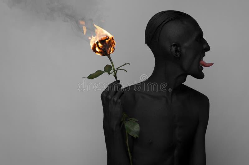 Gotisk och allhelgonaaftontema: en man med svart hud som rymmer en röd ros, svart död som isoleras på en grå bakgrund i studio arkivbilder