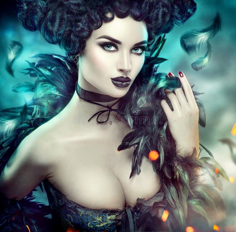 Gotisk sexig ung kvinna halloween Härlig modellflicka med fantasimakeup i gothdräkt med svarta fjädrar royaltyfri fotografi