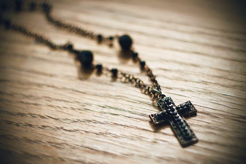 Gotiskt svart kors för metall med svarta pärlor på kedjan arkivfoton