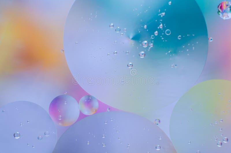 Gotitas coloreadas del aceite en la superficie del agua fotografía de archivo