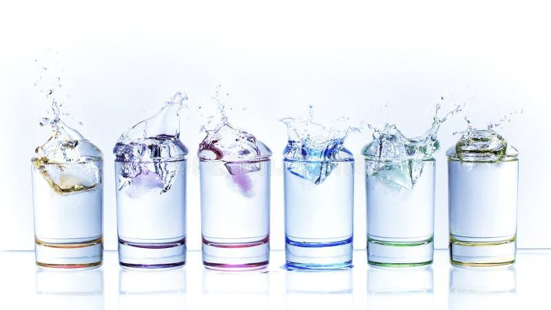 Gotitas de agua de caer un cubo de hielo en un vidrio de líquido imagenes de archivo